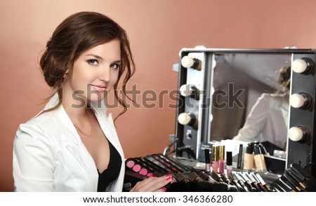 Beauty smiling woman professional stylist. makeup artist over dressing room with mirror. Attractive female face Portrait.   - stock photo