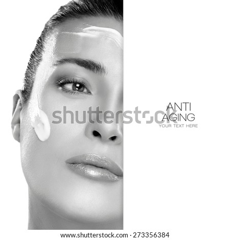 Beauty Spa treatment. Anti Aging and skin care concept with a monochrome portrait of a gorgeous woman with cosmetic cream on her cheek and forehead, blank copy space alongside with sample text. - stock photo