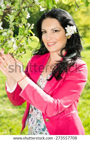 Beauty spring woman smelling apple flowers tree in nature - stock photo