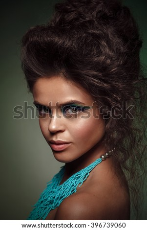 Beauty studio portrait of  sun-tanned woman with bright blue and green make-up. - stock photo