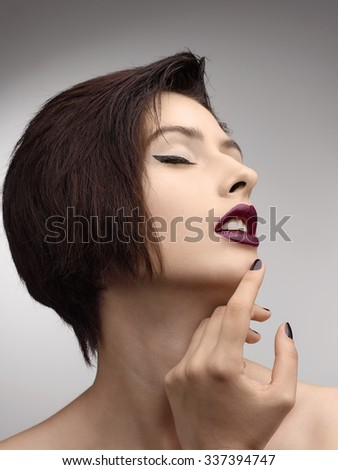 Beauty Style Fashion Model Girl with  Black Manicure it is isolated on a gray background.