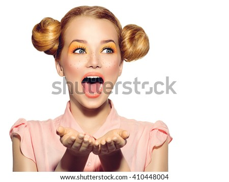 Beauty Surprised Teenager Model Girl. Beautiful Joyful teen girl with freckles, funny red hairstyle and yellow makeup Isolated on a white background showing empty copy space on the open hands for text - stock photo