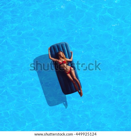 beauty tan glamour lady in red bikini sunbathing by the blue pool outdoors - stock photo