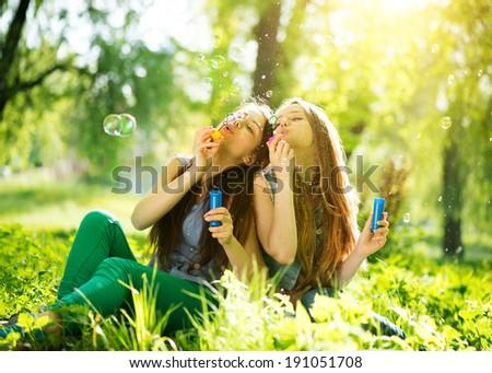 Beauty teen girls having fun outdoors. Beautiful joyful teenagers laughing and blowing soap bubbles in spring park. Girlfriends outdoor.  - stock photo