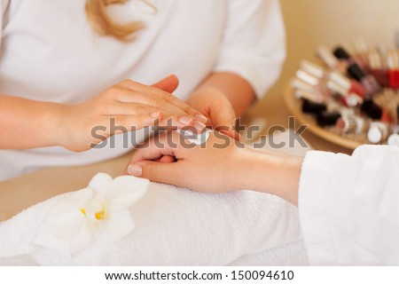 Beauty therapist doing a manicure on the hand of a young woman in a spa or salon, closeup view of their hands - stock photo
