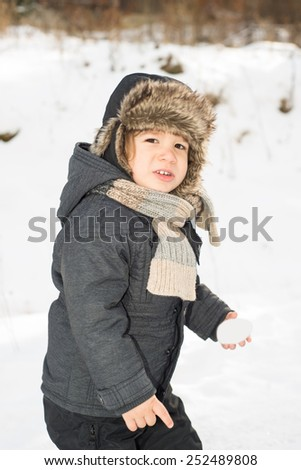 Beauty toddler boy walking  in the snow holding snowball - stock photo