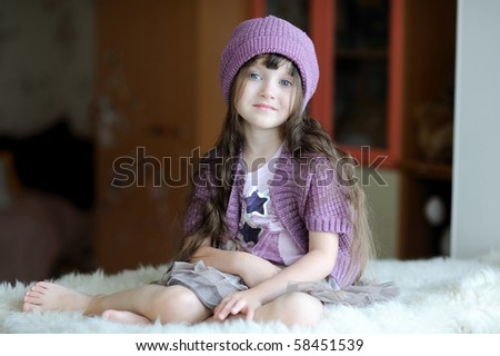 Beauty toddler girl in purple hat sitting on white fur - stock photo