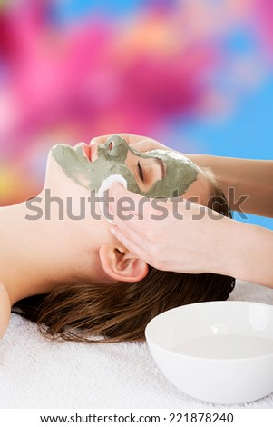 Beauty treatment in spa salon. Woman with facial clay mask. - stock photo