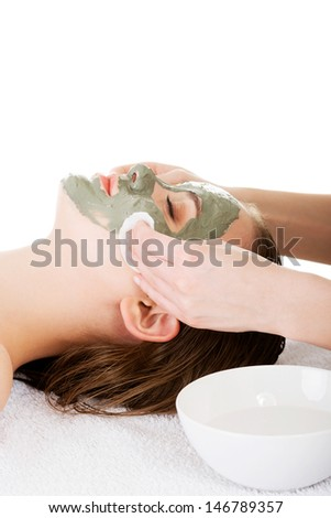 Beauty treatment in spa salon. Woman with facial clay mask. Isolated on white