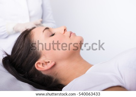 Beauty treatment of the young beautiful female face, doctor's hand in gloves touch face of beautiful young woman isolated on white.
