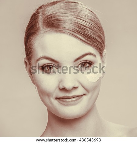 Beauty treatment. Woman applying moisturizing cream skin care product on face studio shot filtered photo