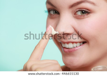 Beauty treatment. Woman applying moisturizing cream skin care product on face studio shot on green blue background