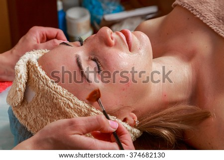 Beauty treatments for problem skin. The girl in the spa salon, applying cream.