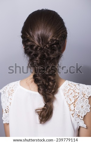 Beauty Wedding Bride Woman Portrait in a white dress with her back on camera, showing bridal hairstyle. Neutral background - stock photo