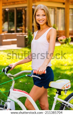 Beauty with bike. Beautiful young woman leaning at her bicycle and smiling while standing outdoors and against house - stock photo
