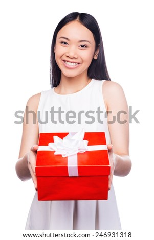 Beauty with gift box. Beautiful young Asian woman holding gift box and smiling while standing against white background - stock photo