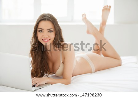Beauty with laptop. Attractive young women in lingerie lying down on the sofa and using computer - stock photo