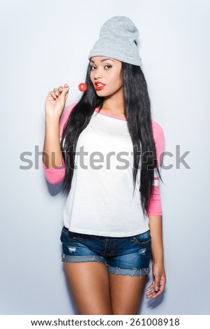 Beauty with lollipop. Beautiful young African woman in funky clothes holding lollipop and looking at camera while standing against grey background - stock photo