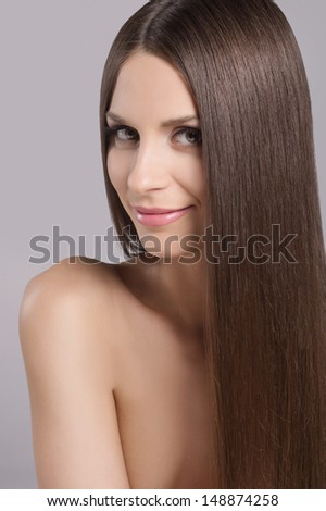 Beauty with long hair. Portrait of attractive young women with beautiful hair looking at camera and smiling while isolated on white