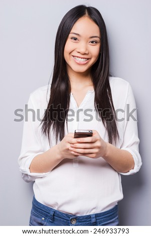 Beauty with phone. Cheerful young Asian woman holding mobile phone and smiling while standing against grey background