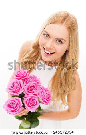 Beauty with roses. Top view of beautiful young blond hair woman holding bouquet with pink roses and smiling while standing isolated on white - stock photo