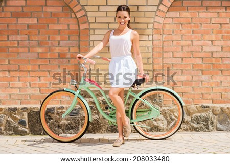 Beauty with vintage bike. Full length of attractive young smiling woman standing near her vintage bicycle  - stock photo
