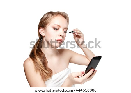 Beauty woman applying makeup. Beautiful girl looking in the mirror and applying cosmetic with mascara - stock photo