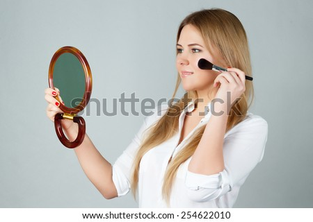 Beauty woman applying makeup. Beautiful girl looking in the mirror and applying cosmetic with a big brush. - stock photo