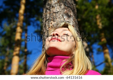 beauty woman breathes near trunk of pine - stock photo