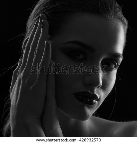 Beauty woman face closeup  Beautiful model girl makeup. Gorgeous sexy brunette lady touching her skin. Perfect make up. Isolated on black background. Dramatic studio portrait. Black and white - stock photo
