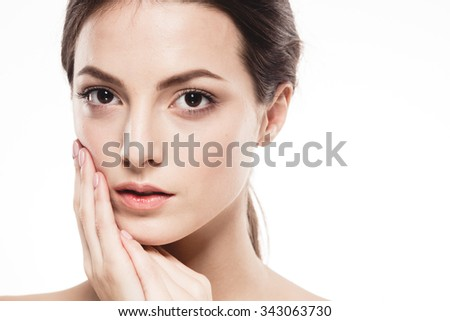 Beauty Woman face Portrait. Beautiful Spa model Girl with Perfect Fresh Clean Skin. Brunette female looking at camera and smiling touching face. Youth and Skin Care Concept. Isolated white background
