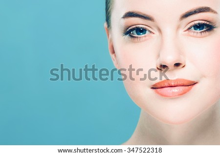 Beauty Woman face Portrait. Beautiful Spa model Girl with Perfect Fresh Clean Skin. Brunette female looking at camera and smiling. Youth and Skin Care Concept.Blue background gray - stock photo