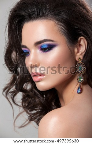 Beauty woman face with beautiful make-up color . Dark hair , raised hair , jewelry on his neck , clean skin , beautiful face . Portrait shot in studio on a grey background .