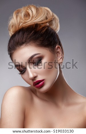 Beauty woman face with beautiful make-up colors. Dark hair, a crown on his head, clear skin, beautiful face, plump lips. Portrait shot in studio on a gray background.