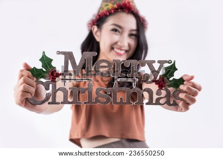 Beauty woman holding Christmas sign. Christmas woman portrait of a cute, beautiful smiling mixed Asian model. Isolated on white background. (Focus on Christmas's sign) - stock photo