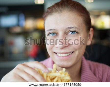 beauty woman in cafe eating hamburger - stock photo