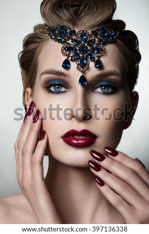 Beauty Woman in jewelry. Professional Makeup. Burgundy red Lipstick. Beautiful Fashion Model Girl Face. Beauty Red Lip. Perfect manicure. - stock photo