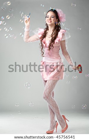 beauty woman in pink dress with soap bubbles