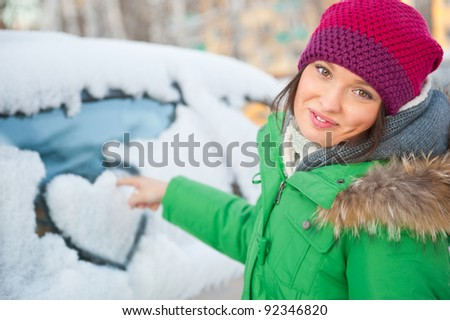 Beauty woman in the winter clothes drawing heart on car