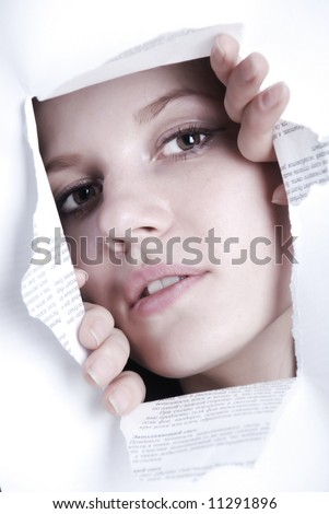 Beauty woman looking through hole in white paper - stock photo