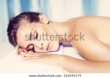 beauty woman lying on towel,small amount of grain added,  wellness and spa concept