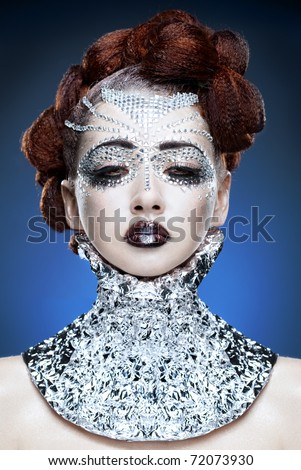 beauty woman makeup with crystals on face on blue background - stock photo