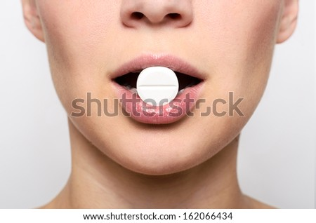 Beauty woman mouth with red lips and medicine pill on grey background