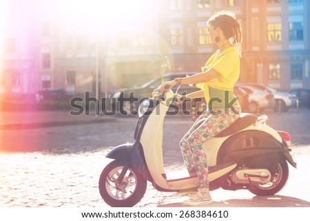 Beauty woman on scooter. Young and beautiful woman riding scooter along the street - stock photo