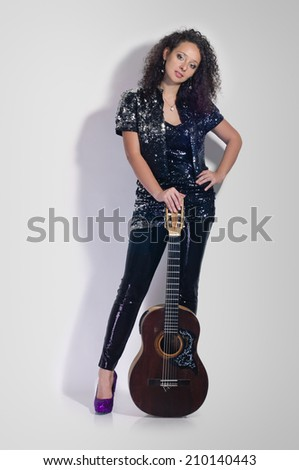 beauty woman player with classical guitar full length on grey