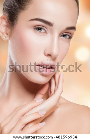 Beauty Woman Portrait. Beautiful Spa Girl Touching her Face and smiling. Perfect Fresh Skin. Pure Beauty Model Female looking at camera. Youth and Skin Care Concept. Isolated on background