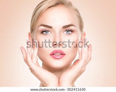 Beauty Woman Portrait. Beautiful Spa Girl Touching her Face. Perfect Fresh Skin. Pure Beauty Model Female looking at camera. Youth and Skin Care Concept.  - stock photo