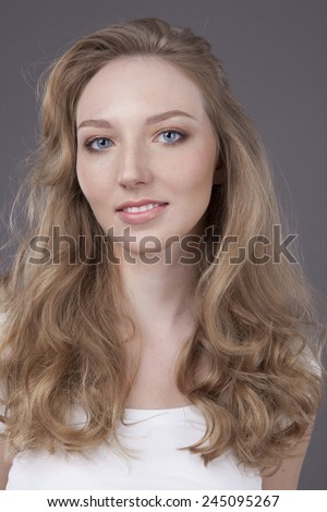 beauty woman portrait of teen girl beautiful cheerful enjoying with long blonde hair and clean skin isolated on grey background