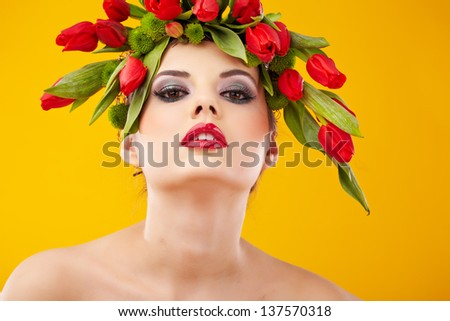 beauty woman portrait with wreath from flowers on head over yellow  background