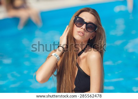 Beauty woman relax near swimming pool on sunny day - stock photo